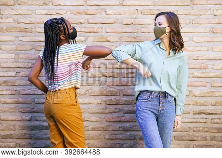 Multiethnic Young Women Wearing Masks Greeting At Each Other With Their Elbows