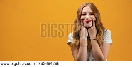 Young Beautiful Woman In Casual T-shirt Standing And Pretends To Smile, Stretches Her Mouth Into A S