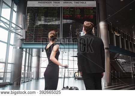 Man And Woman Looking A The Timetable A The Station