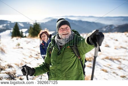 Senior Couple Hikers With Nordic Walking Poles In Snow-covered Winter Nature.