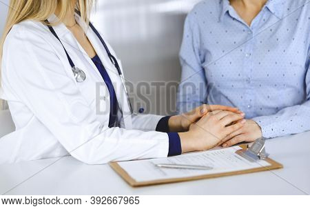Unknown Woman-doctor Is Holding Her Patients Hands To Reassure A Patient, While Sitting Together At