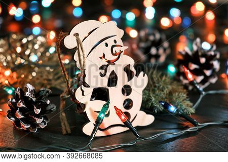 Decorative Wooden Snowman Against The Backdrop Of Blurred Christmas Lights And Other Seasonal Decora