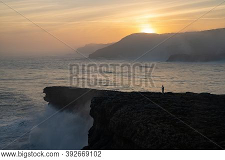 A View Of Huge Storm Surge Ocean Waves Crashing Onto Shore And Cliffs At Sunrise With A Person Stand