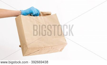 A Man In Protective Mask Is Delivering Food On A Bicycle. Online Shopping And Express Delivery . Qua