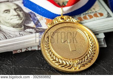 Bribe In Sports For Victory. Gold Medal Award And A Stack Of Money Dollars