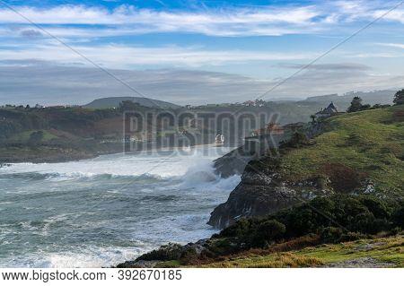 A View Of Huge Storm Surge Ocean Waves Crashing Onto Shore And Cliffs At La Sorrozuela Village In Sp
