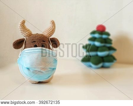 Crochet Soft Toy Bull Cow In Blue Medical Protective Mask. On A Light Background With A Toy Fir Tree