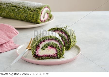 Green Spinach Roll Cake With Cream Cheese And Raspberries Filling On Plate. Restaurant, Bakery Menu