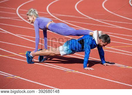 Pumping Up Muscles. Athletic Man And Woman In Stand Plank. Male And Female Coach On Stadium Arena. H