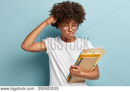 Puzzled Questioned Pupil Scratches Head, Looks With Doubt And Displeased Expression At Papers, Carri