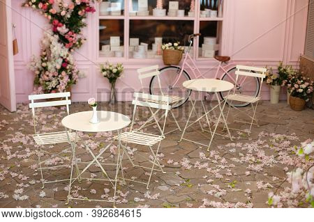 Empty Cafe Terrace With White Tables And Chairs. Pink Exterior Of The Cafe Restaurant. Interior Stre