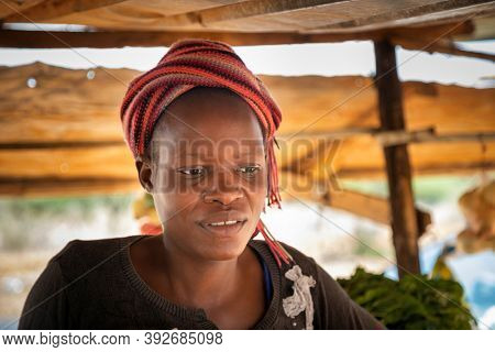 african woman street vendor with entrepreneurial spirit, selling vegetables on a wooden table