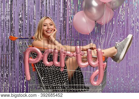 Glad Blonde Girlfriend In Shopping Cart, Celebrates Birthday, Wears Fashionable Clothes, Poses Over