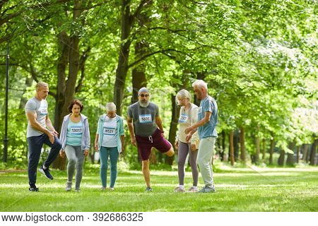 Long Shot Of Active Seniors Taking Part In Summer Marathon Race Standing Together Somewhere In Park