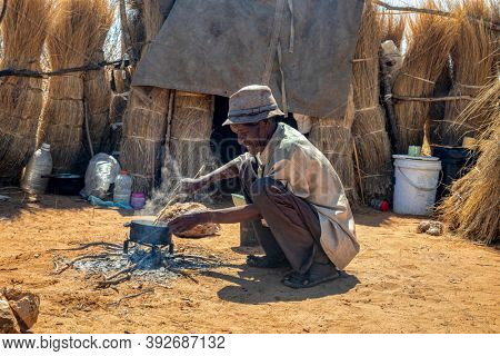 old African man cooking in the outdoors improvised kitchen