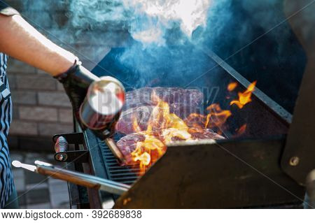 A professional cook prepares meat on the grill outdoor, food or catering concept
