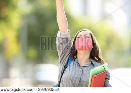 Front View Portrait Of An Excited Student Wearing Mask Raising Arm In The Street Celebrating Success