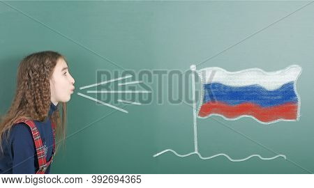 Pre-adolescent Girl Blowing On The School Board Drawn On The Blackboard Russian Federation Flag. Hig
