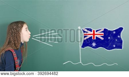 Pre-adolescent Girl Blowing On The School Board Drawn On The Blackboard Australia Flag. High Resolut
