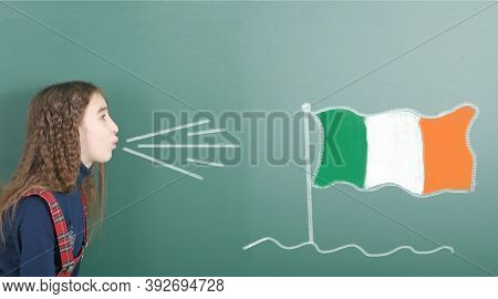 Pre-adolescent Girl Blowing On The School Board Drawn On The Blackboard Ireland Flag. High Resolutio