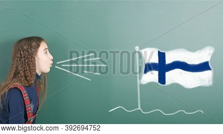 Pre-adolescent Girl Blowing On The School Board Drawn On The Blackboard Finland Flag. High Resolutio