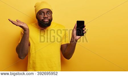 Hesitant Confused Man Choose New Smart Phone, Holds Modern Electronic Device With Mock Up Screen, Ra