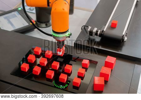 Pick And Place Robotic Clamp Arm Manipulator Moving Red Toy Blocks At Modern Robot Exhibition, Trade