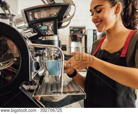 Smiling Female Barista Using Coffee Maker In Cafeteria. Woman In Apron Preparing Espresso.