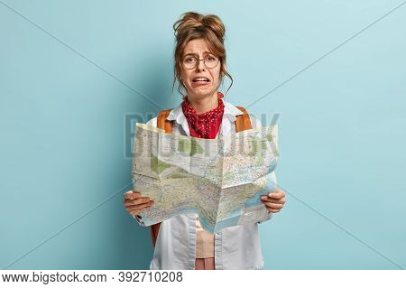 Crying Female Tourist Lost In Unknown Destination, Holds Map, Tries To Find Way, Looks With Dissatis