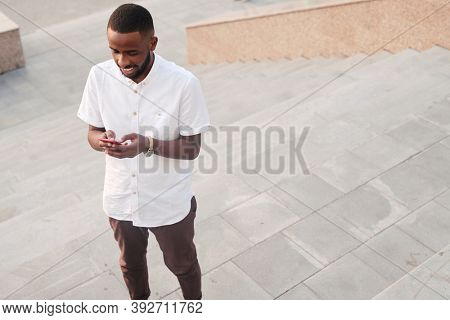 Young bearded African businessman in white shirt and brown pants messaging while standing on wide tiled staircase in front of camera