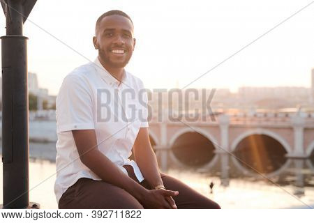 Happy young African businessman in white shirt and brown pants sitting in front of camera in urban environment against riverside and cityscape