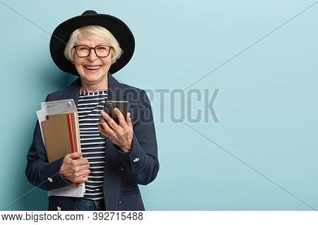 Cheerful Female Moderator Socialises Online, Holds Modern Gadget, Receives Notification, Holds Paper
