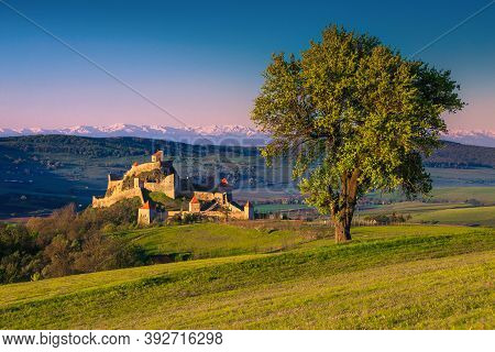 Amazing Morning Scenery With Rupea Fortress And Snowy Mountains In Background. Great Touristic And E