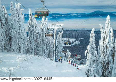 Skiers Enjoying The View On The Ski Lift. Stunning Place With Snowy Pine Trees And Skiers On The Slo