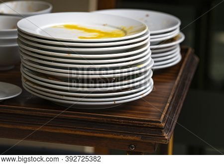 Used White Food Plates Stacked In Layers, Food Residue In The Dish. Food Plate On Wooden Table, Wait