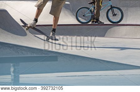 Young Active Men Riding Skateboard And Bmx Bike In Concrete Skatepark