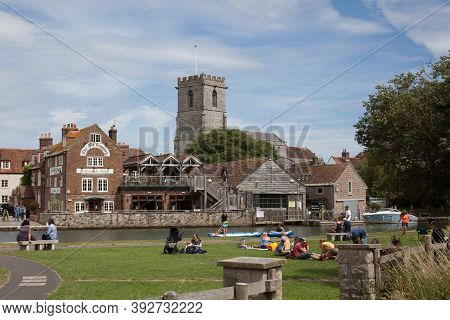 People Relaxing In The Sun By The River Frome At Wareham In Dorset In The Uk, Taken On The 23rd July