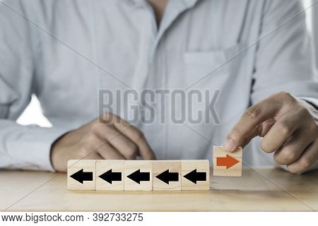 Businessman Putting Red Arrow Move Opposite Direction Among Black Arrow Which Print Screen On Cubes