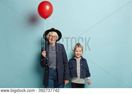 Photo Of Retired Senior Woman Holds Hand Of Little Adorable Granddaughter, Come On Party, Hold Red B