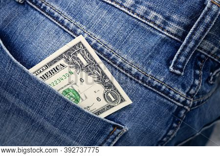 One Dollar Bill In The Back Pocket Of Jeans. One Buck In A Denim Pocket.