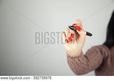 Young Woman Holding A Black Marker And Writes Something On A Light Background
