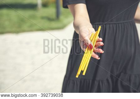 A Womans Hand Holds  Wax Candles In An Orthodox Church