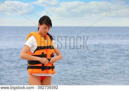 Beautiful Female Lifeguard Putting On Life Vest Near Sea