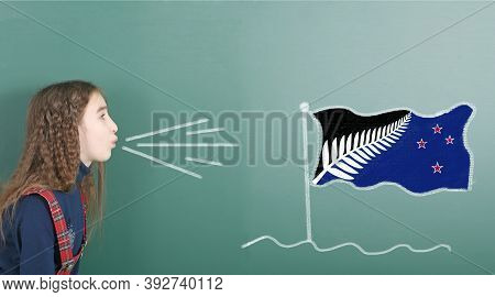 Pre-adolescent Girl Blowing On The School Board Drawn On The Blackboard New Zealand Flag. High Resol