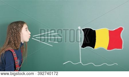 Pre-adolescent Girl Blowing On The School Board Drawn On The Blackboard Belgium Flag. High Resolutio