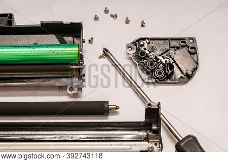 A Set Of Components Of The Disassembled Laser Toner Cartridge, Screwdriver And Bolts, Lies On A Ligh