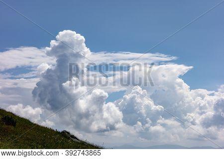 High Cumulonimbus Clouds At The Blue Sky With Landscape In A Corner