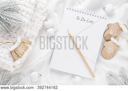Christmas Decorations And Notepad With To Do List Or Goals And Dreams On White Background. Flat Lay,