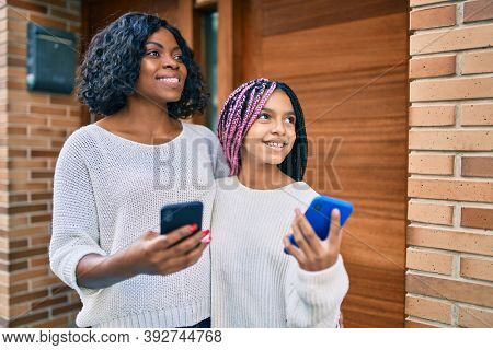 African american mother and daugther hugging and using smartphone at the city.