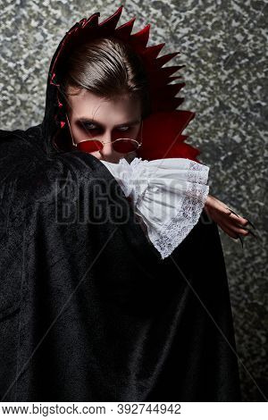 Portrait of a traditional vampire aristocrat of the 19th century covering his face with a Cape. Count Dracula. Halloween.